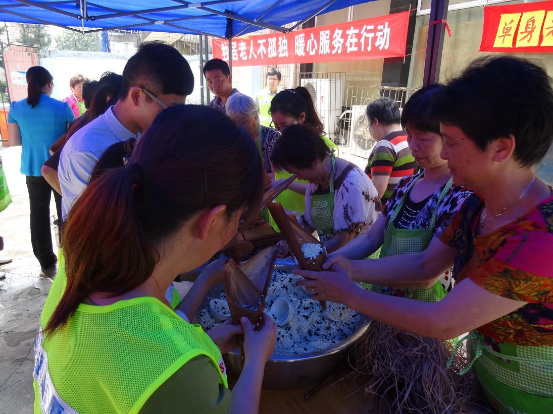 """新典社区联合公交通成志愿者开展了""""包粽子,迎端午""""庆佳节活动."""